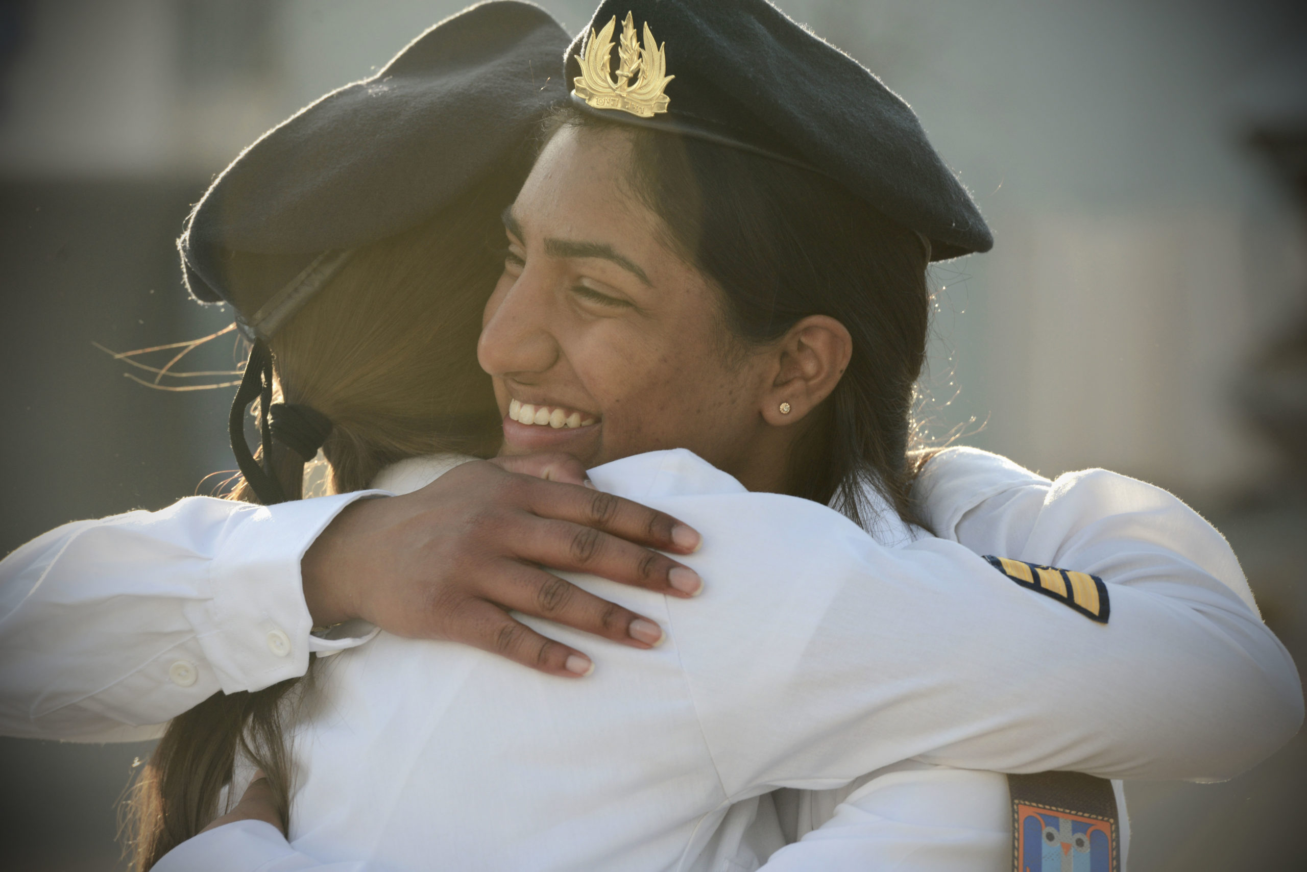To women hug after completing training to enter the IDF's Navy